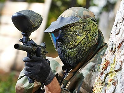 A man dressed in camouflage with paint on helmet holding a paintball gun