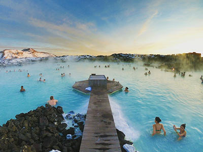 A view of the Blue Lagoon with various people in it and a blue and yellow sky