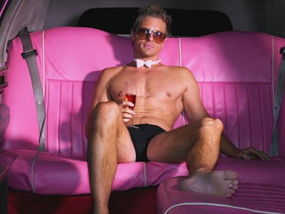 A topless man holding a glass of alcohol, sitting on pink leather seats in a vehicle