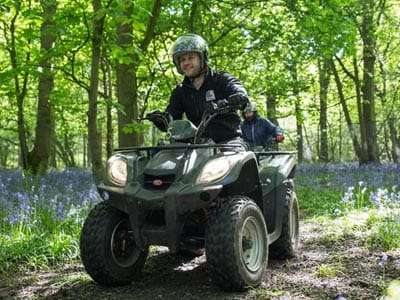 Image of a guy on a quad bike in the forest on a track