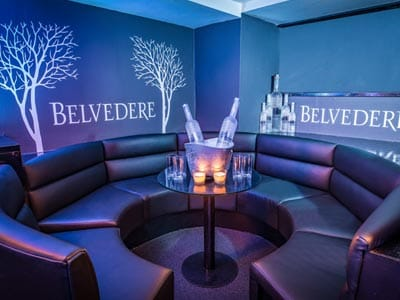 Image of a rounded booth with a small round table with a ice bucket filled with champayne and vodka