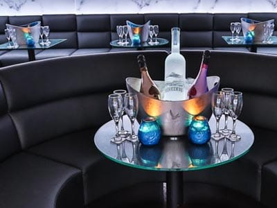 Image of a ice bucket with two bottles of champayne and a bottle of vodka on a table with two blue glass tea lights and siz champayne glasses