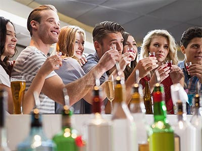 A group of men and women drinking shots