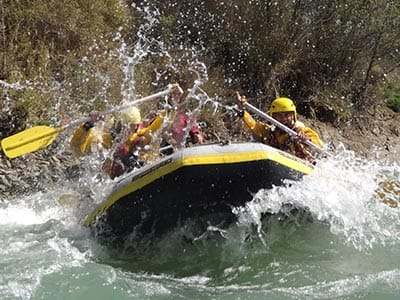 Image of a group of people inside a raft in choppy waters with yellow helmets and yellow owes