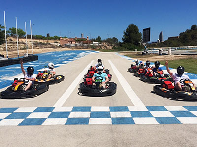 An outdoor racetrack with people in go-karts at the starting position