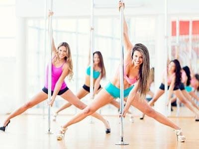 Image of a group of women dancing on poles in a studio wearing heels