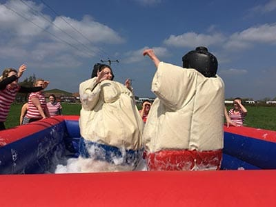 Image of two women in an inflatable pool filled with bubbles wearing sumo wrestling costumes