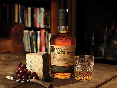 A bottle of Glen Garloch whiskey next to a tumbler and a block of cheese on a table