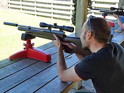 A man aiming with an air rifle on a red stand, set on a wooden table