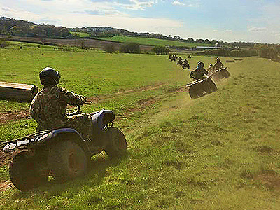 A line of people driving quad bikes in a field