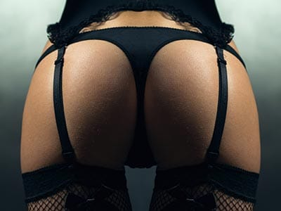 Image of a womans bum wearing a thong and suspenders