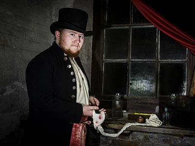 Image of a man wearing a black top hat and a black suit jacket with gold buttons standing wiping blood off a knife onto a piece cloth in a dark room