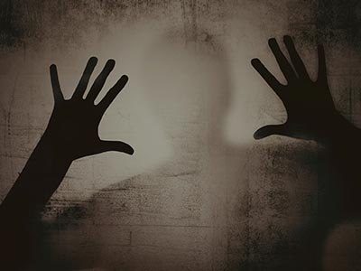 A silhouette of a person holding their hands up against a wall