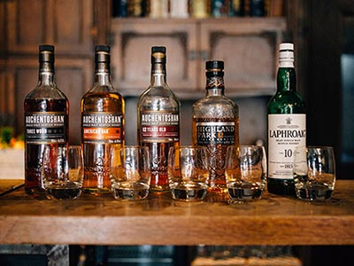 A line of various bottles of Whiskey on a bar