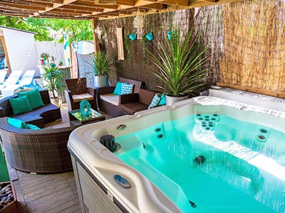 An outdoor space with a hot tub in the foreground