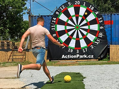 A man about to kick a football onto a large darts target