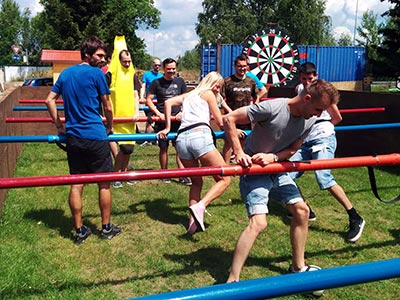 A group of people playing human table football on some grass