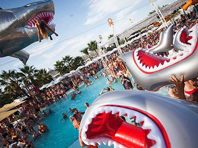 People holding up inflatable sharks, with a large pool party in the background
