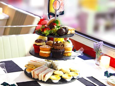 A serving tray with three tiers of cakes and sandwiches