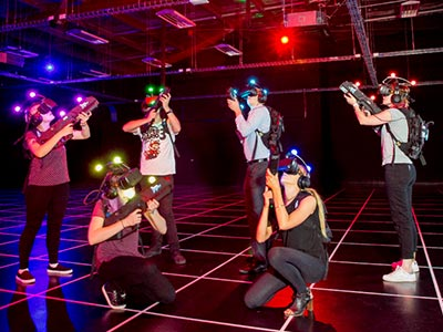 A group of people in a warehouse wearing VR helmets and posing with guns