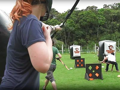 Someone aiming a bow and arrow at people hiding behind inflatable obstacles