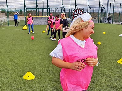 A field outside, with a girl in the foreground wearing a pink bib and other girls in the background