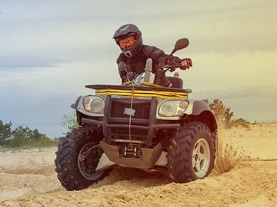Image of a guy on a quad bike on the sand