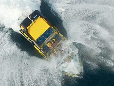 Image of a yellow speed boat splashing waves in the water