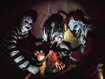 A dark room with three people dressed up in scary costumes
