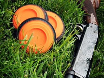 Image of a shotgun on grass alongside three clays