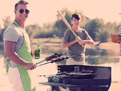A man wearing sunglasses cooking on a bbq and a man holding a baseball bat