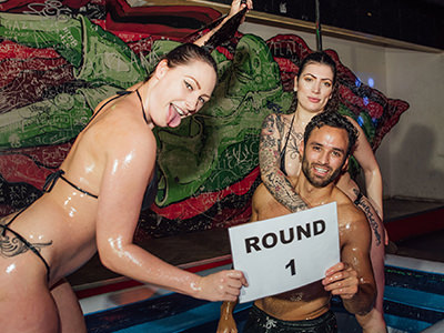 Two women and a man in an inflatable pool holding a sign that reads 'round 1'