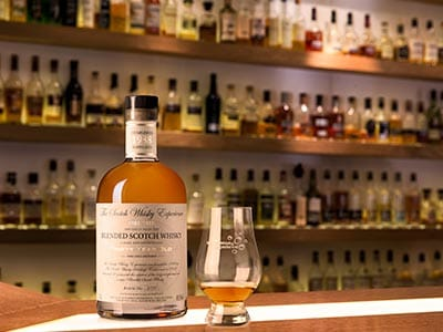 Image of a bottle of whiskey on wooden bar top with a whiskey glass and a whiskey display in the background