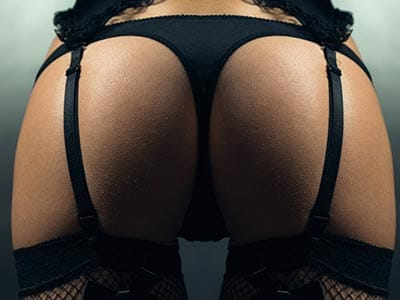Image of a female wearing a black thong and black suspenders