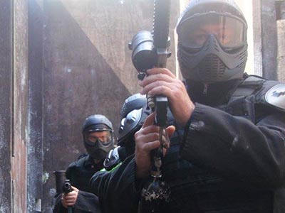 Three people in SWAT outfits, carrying guns