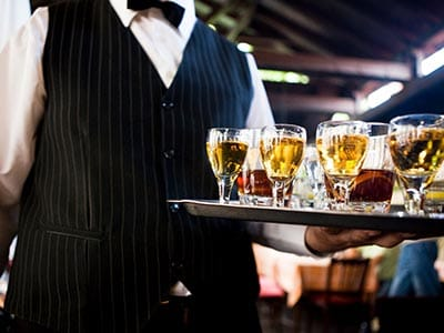 Image of a waiter carrying a tray of alcoholic drinks