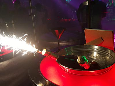 Bottles of alcohol in an ice bucket on a table, with a sparkler