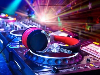 A pair of DJ headphones on a mixing desk, in a club