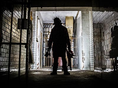 Someone in shadow carrying weapons in a dark cell