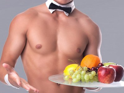 A semi-naked man wearing a black and white bowtie collar and holding a tray of fruit