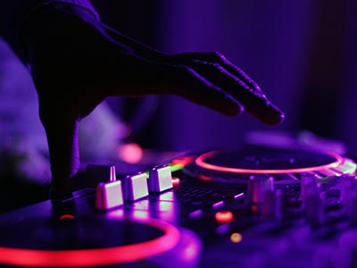 A close up of a DJ's hand on some decks with purple and red lights