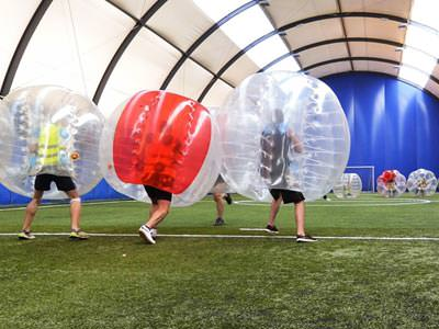 Image of a group of men inside a inflatable ball on a football pitch