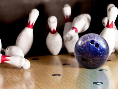 Image of a bowling bowl knocking down pins