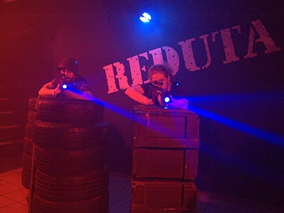 Two people aiming laser guns whilst hiding behind obstacles
