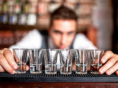 A bartender lining up some shot glasses on the bar