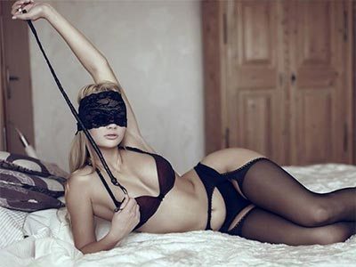 A woman blindfolded wearing lingerie and sitting on a bed holding a whip