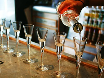 Vodka getting poured into various glasses, on a bar