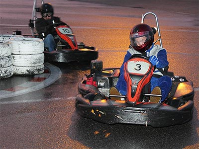 Two people driving go karts on a track