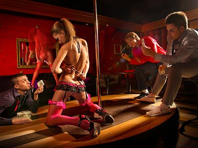 Image of a woman in pink underwear and suspenders kneeling on a table with a pole and three men sitting around her drinkinh and holding money