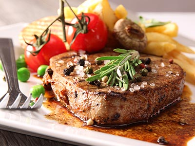 Steak and chips on a plate with garnish
